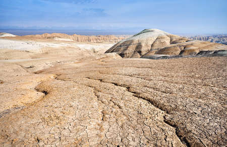 Landscape of cracked ground and mountains in the desert. National desert park Altyn Emel in Kazakhstan Banco de Imagens