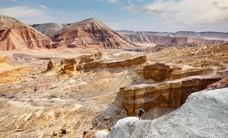 Tourist walking at the trail on surreal yellow mountains in desert park Altyn Emel in Kazakhstan Stock Photo