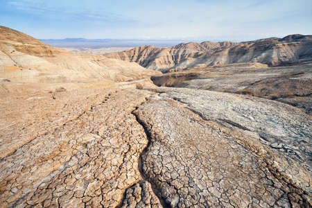 Landscape of cracked ground and mountains in the desert. National desert park Altyn Emel in Kazakhstan Stock fotó