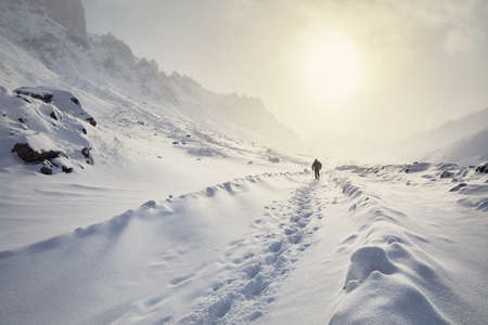 Tourist on the snow road in the beautiful mountains at winter