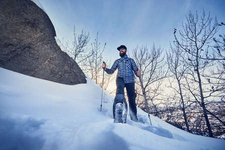 Happy Hiker with beard in snowshoes at winter forest at blue sky background Foto de archivo - 115559133