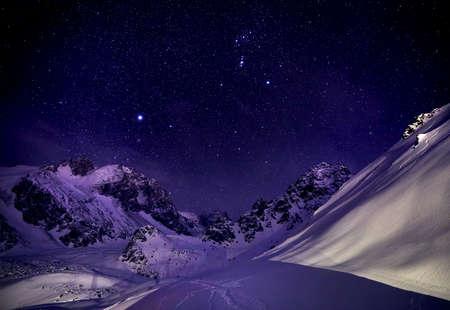 Bellissimo paesaggio invernale delle montagne innevate contro il cielo notturno stellato
