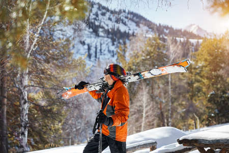Man in orange jacket holding ski and looking at snow mountain at sunny day