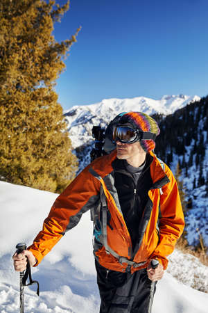 Portrait of skier in orange jacket and mask at snow mountain  at sunny day
