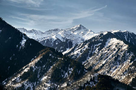High mountains with snow and pine trees and peak against blue sky in Kazakhstan at winter time Stock Photo