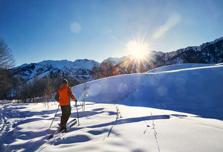 Man skiing on fresh powder snow at the mountains against sunset sun in Almaty, Kazakhstan Banque d'images
