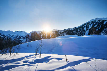 Sunrise in the mountains with snow and high peaks against blue sky