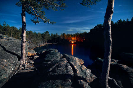 Camp fire in the forest near lake at night starry sky Reklamní fotografie