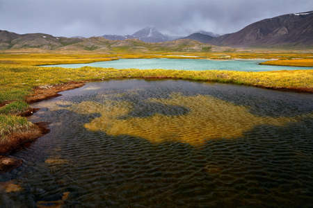 Mountain Lake in the valley against cloudy sky in Kyrgyzstan Stock Photo