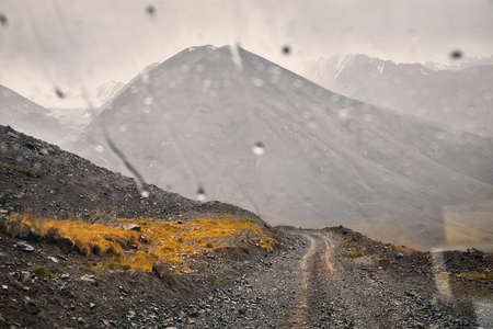 Road in beautiful mountain valley viewed from the car window with raindrops. Travel and adventure concept.
