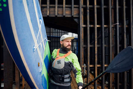 Portrait of bearded athlete in wetsuit holding surfboard and paddle
