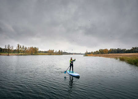 Man training on paddleboard in the lake against overcast sky Stock Photo
