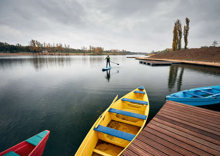 Man on the paddleboard in the lake against overcast sky and pier with colorful boats at foreground