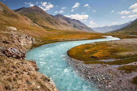 Beautiful river in the mountain valley against blue sky in Kyrgyzstan Stock fotó