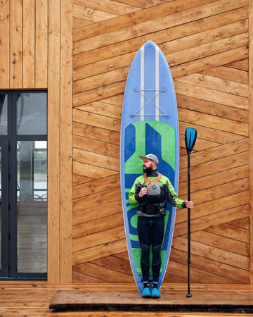 Bearded athlete in wetsuit with blue surfboard and paddle at wooden wall