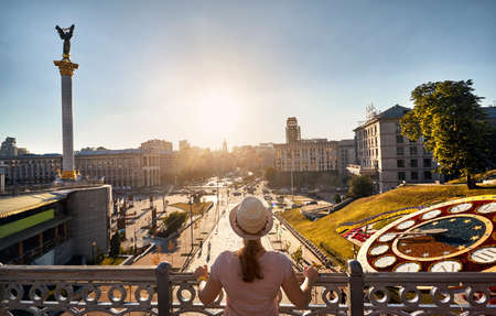 Woman tourist is looking at famous Independence Square Maidan Nezalezhnosti at sunset in Kiev, Ukraine