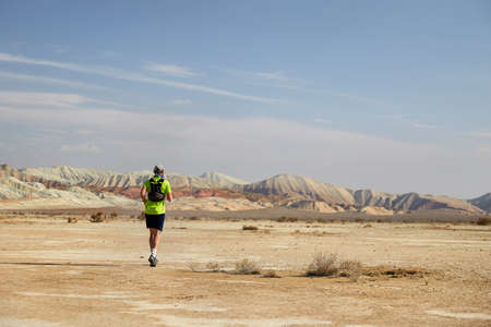 Runner athlete with backpack running on the wild trail at red mountains in the desert Stock Photo