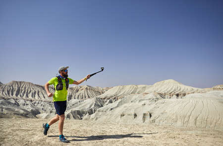 Runner athlete with beard running on at white mountains in the desert with action camera