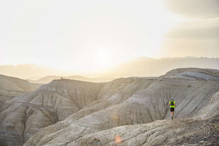 Runner athlete with backpack running on the wild trail at mountains in the desert at sunset