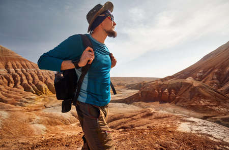 Portrait of Tourist with backpack and hat at the surreal red mountains  against blue sky Фото со стока