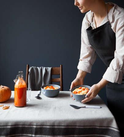 Woman serve breakfast table with vegan pumpkin porridge and fresh juice in Scandinavian style on grey background.