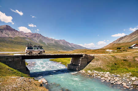 White van with bicycle on the roof is crossing river by bridge in the mountains in Kyrgyzstan