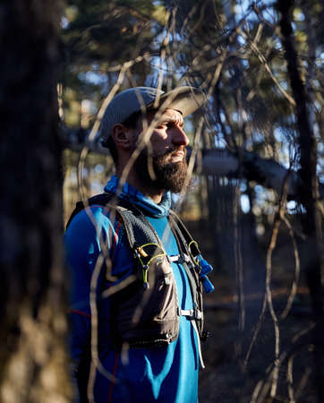 Portrait of runner athlete with beard in blue shirt in the forest