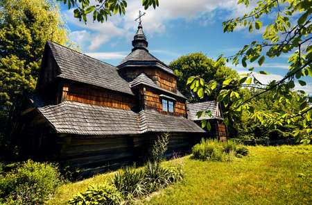 Old wooden church surrounded by lush vegetation in the traditional village of Eastern Europe.
