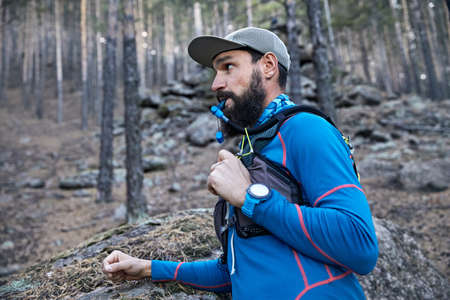 Portrait of runner athlete with beard drinking water from the tube of hydropack in the forest