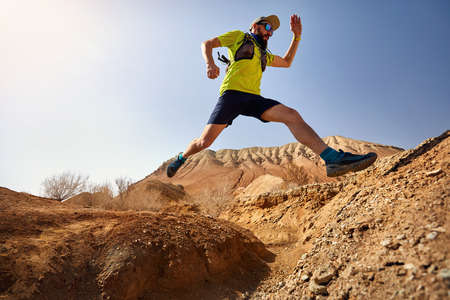 Runner athlete with beard jump over the canyon on the wild trail at red mountains in the desert Stock Photo
