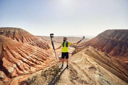 Bearded man holding two cameras on the top of the mountain in the desert Stockfoto - 121192689