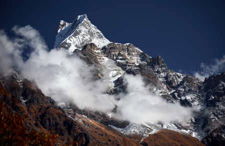 Machapuchare peak surrounded by clouds against blue sky in the Himalayas, Nepal.