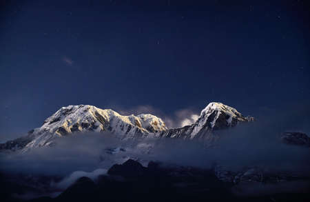 Snowy Annapurna and Hinchuli mountains at night starry sky in Nepal