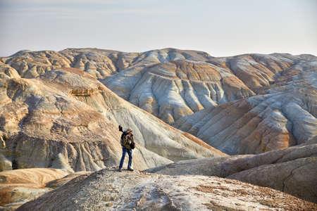 Touriste avec appareil photo et sac à dos dans les montagnes désertiques surréalistes