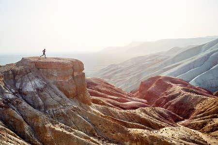 Silhouette des Läufers auf dem großen Felsen im Canyon mit roten Wüstenbergen