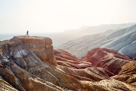 Silhouette of runner athlete on the big rock in canyon with red desert mountains 版權商用圖片 - 121192757