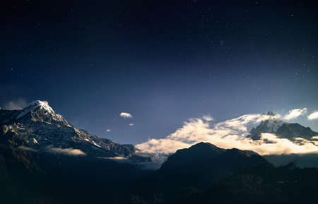 Snowy Annapurna and Machapuchare mountains at night starry sky in Nepal