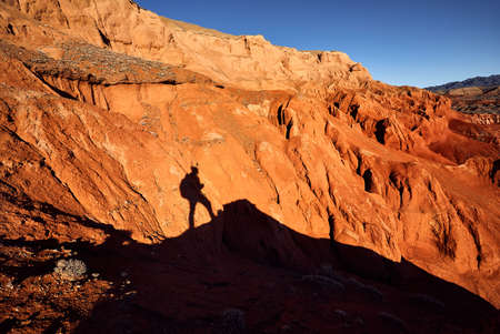 Tourist shadow at Red mountains in the desert canyon against blue sky in Kazakhstan