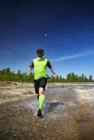 Man with grey beard running on the river with splashes in the morning. Healthy lifestyle concept