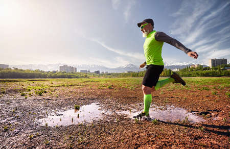 Man with grey beard running on the dirty trail with water splashes at mountain background in the morning. Healthy lifestyle concept