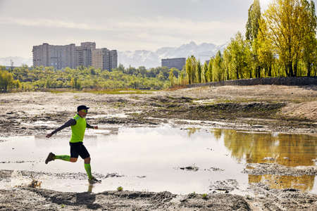 Man with grey beard running on the dirty trail with pool at mountain background in the morning. Healthy lifestyle concept Stok Fotoğraf