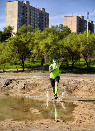 Man with grey beard running on the dirty trail with pool at city park in the morning. Healthy lifestyle concept Stok Fotoğraf