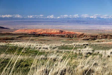 Landscape of red mountains in the steppe surrounded by snowy mountains in Kazakhstan Stock fotó