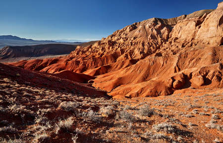 Red mountains in the desert canyon against blue sky in Kazakhstan