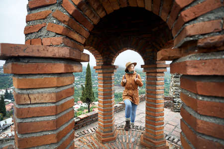 Tourist woman in hat walking in the arch of old church at autumn foggy day in Signagi, Georgia
