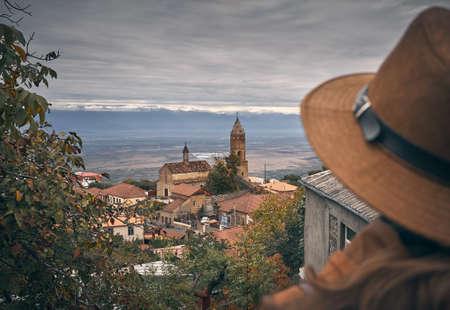 Alte Kirche mit Turm in Signagi-Stadt am grauen bewölkten Himmel und Frau mit Hut unscharf in Georgia