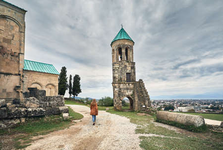 Frau zu Fuß zum Kapellenturm der Bagrati-Kirche bei bedecktem Himmel in Kutaisi, Georgia