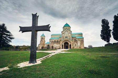 Big iron Cross in front of Bagrati church at overcast sky in Kutaisi, Georgia