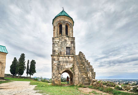 Woman tourist in the arch of Chapel tower of Bagrati church at overcast sky in Kutaisi, Georgia