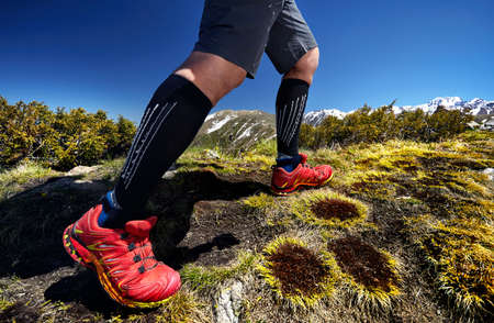 Close up of hiker legs in red shoes are climbing in the mountains at blue sky